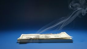 SLOW MOTION: Heap of paper money US dollar smoking. SLOW: Heap of paper money US dollar smoking stock footage