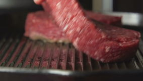 SLOW: Human hand puts a beefsteak on grill