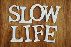 Slow Life alphabet letter with space copy on wooden background stock image