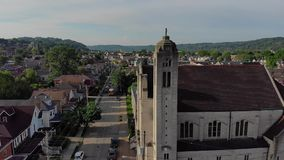 Slow lowering aerial establishing shot of small town and church stock footage
