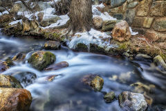Slow Melting Ice on the River. Ice hangs on the side of the Big Cottonwood Canyon river in the Wasatch mountains of Utah USA shot in slow motion in January Stock Images