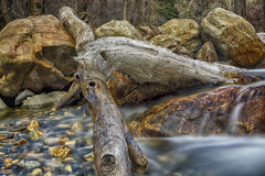 The Slow Melting Snow. Ice hangs on a log in the sprigtime in the Wasatch National Forest in Utah USA shot in slow exposure Stock Photo