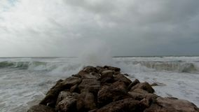 A slow-mo footage of a storm at the beach with huge wave crashing on a rocky groyne breakwater.  stock footage