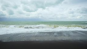 Slow mo long wave on the black shore. Slow mo long wave is gaining strength on a black pebble beach under a cloudy sky stock footage