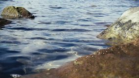 Slow mo slight excitement of the water surface among the stones in the water. Slow mo small bubbles on the water surface of transparent blue water among large stock footage
