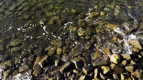 Slow Mo wave rolls to shore. Slow Motion waves wave on a stony shore. View from above stock video