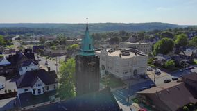 Slow morning approach to church Steeple in small town. A slow morning or evening aerial approach to a church steeple in a small town's business district stock footage