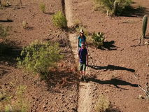 Slow Motion Aerial Shot of Desert Hikers on Rugged Trail stock video footage