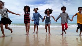 Slow motion, African-American children are holding hands running on the beach in the summer