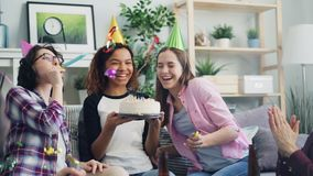 Slow motion of African American woman blowing candles birthday cake with friends. Slow motion of happy African American woman blowing candles on birthday cake stock video footage