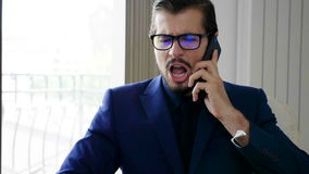Slow motion of angry businessman in suit talking on mobile phone stock footage