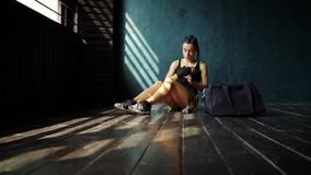 Slow motion approaching fit young woman with sports bag sitting on floor and wrapping hand with tape. Slow motion approaching fit young woman with bag sitting on stock footage