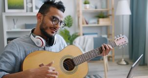 Slow motion of Arabian musician playing the guitar in front of laptop at home. Slow motion of handsome Arabian musician playing the guitar in front of laptop stock video footage