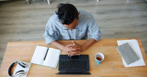 Slow motion of Arabian office worker typing using laptop then stretching arms. Relaxing in workplace. Modern technology, employment and people concept stock footage