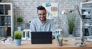 Slow motion of Arabian office worker using laptop smiling at desk in workplace. Slow motion of Arabian office worker handsome man in glasses using laptop smiling stock footage