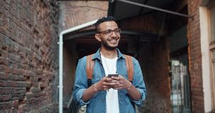 Slow motion of Arabian student using smartphone and laughing standing outdoors. In the street alone touching screen. Happiness, youth and devices concept stock footage