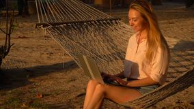 Slow motion architect young woman with laptop rejoicing at good news. Slow motion architect lady with laptop sitting on hammock, smiling girl on vacation stock video footage
