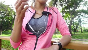 Slow motion - Asian beautiful woman in fitness outfits are using a smartwatch for listen to music, talking on the phone. Slow motion - Asian beautiful woman in stock video