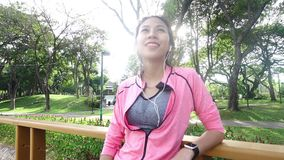 Slow motion - Asian beautiful woman in fitness outfits are using a smartwatch for listen to music, talking on the phone. Slow motion - Asian beautiful woman in stock footage