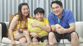Slow motion of asian family father mother and son on couch, Looking at camera with smile face.  stock footage