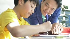 Slow motion of asian father with son doing his homework at home with smile face. stock footage