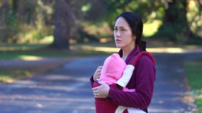 Slow motion of Asian Mother and baby outdoors in a park stock video footage