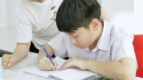 Slow motion of Asian mother helping her son doing homework on white table. stock video