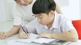 Slow motion of Asian mother helping her son doing homework on white table.