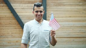 Slow motion of attractive Arabian guy holding national flag of the USA smiling. Slow motion portrait of attractive Arabian guy holding national flag of the USA stock footage