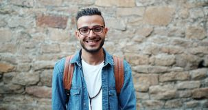 Slow motion of attractive Arabian student smiling standing outdoors alone. Looking at camera. Modern young people, lifestyle and urban style concept stock video