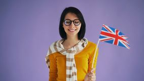Slow motion of attractive British lady holding flag of Great Britain smiling. Slow motion portrait of attractive British lady holding flag of Great Britain stock video