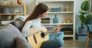 Slow motion of attractive girl enjoying music playing guitar in apartment alone