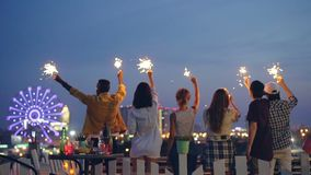 Slow motion of attractive young people holding burning sparklers standing on rooftop with their backs to the camera at stock video