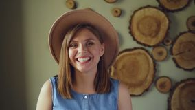 Slow motion of attractive young woman with blond hair wearing trendy hat and denim top looking at camera, laughing and. Smiling. Modern people and positive stock video footage