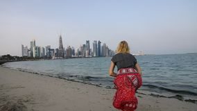 Tourism in Doha West Bay. SLOW MOTION: Back of caucasian woman jumping on the beach with the modern skyscrapers of Doha West Bay along Corniche promenade on Doha stock footage