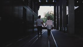 Slow motion back view happy romantic couple walking together holding hands on rails under dark evening city bridge. Young man and woman spending time of stock footage