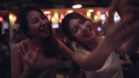 Slow motion - Backpacker Asian women lesbian lgbt couple taking selfie drinking alcohol or beer with friend and party.