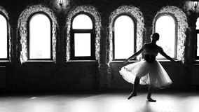 Slow motion ballerina practicing dance before performance. Beautiful elegant ballet girl in white dress dancing in studio. Monochrome style stock video footage