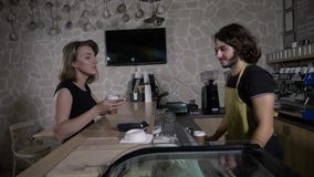 Slow motion of a barista male serving coffee to go while the female customer pays using her smartphone and leaves smiling -. Slow motion of a barista male stock video footage