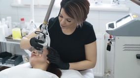 Slow motion beautician does laser facial peeling for woman with special device. Concept beauty center, medical clinic stock video