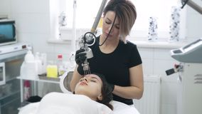 Slow motion beautician does laser facial peeling for woman with special device. Concept beauty center, medical clinic stock footage