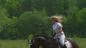 SLOW MOTION:  A beautiful girl in white hair and white clothes is riding a black brown stallion. stock footage