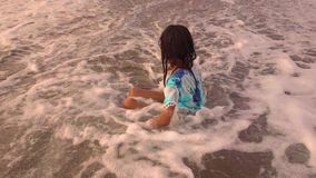 Slow motion beautiful  happy Asian Indonesian child girl playing carefree on the beach having fun in the sea playing with waves stock footage