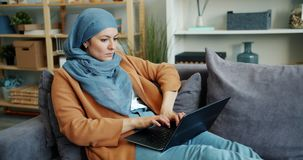 Slow motion of woman in hijab using laptop typing working on couch at home. Slow motion of beautiful Middle Eastern woman in hijab using laptop typing working stock video footage