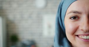 Slow motion of beautiful mixed race lady in hijab half face on brick background. Slow motion of beautiful mixed race lady in hijab half face on brick wall stock footage