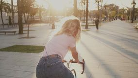 Pretty girl on her urban vintage bicycle at sunset. Slow motion of beautiful pretty young girl, woman with blonde hair look back at camera with happy, dreamy and stock video