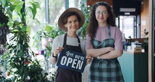 Slow motion of beautiful women holding we are open sign standing in flower shop. Slow motion of beautiful women coworkers holding we are open sign standing in stock footage