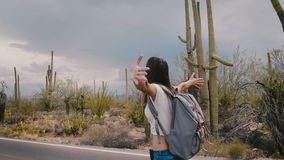 Slow motion beautiful young happy tourist woman walking along desert national park road with arms open before a storm.