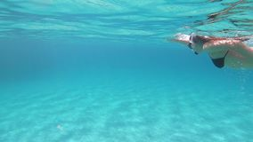 Slow motion of a beautiful young woman in a black bikini taken by swimming underwater in blue water with mask and snorkel on an. Impressive transparent blue and stock video
