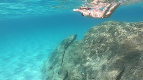 Slow motion of a beautiful young woman in a black bikini taken from underwater swimming in the blue water with mask and snorkeling. On the seabed of rocks and stock video footage